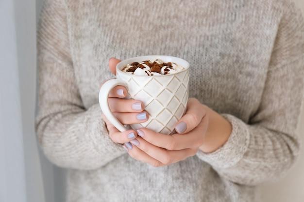 Giovane donna con una tazza di gustosa bevanda al cacao a casa, primo piano