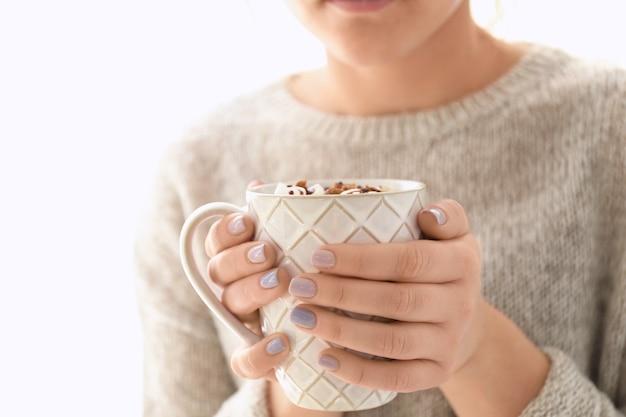 Giovane donna con una tazza di gustosa bevanda al cacao su sfondo bianco, primo piano