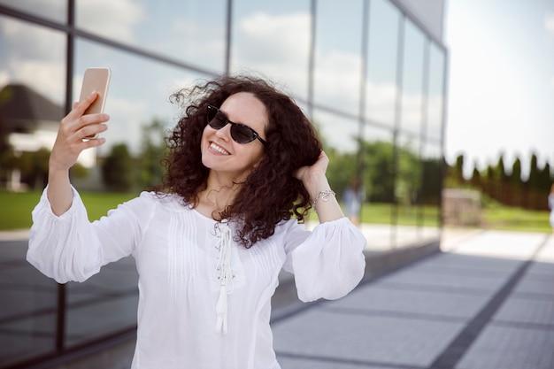 Giovane donna con capelli ricci fuori facendo un selfie con lo smartphone.