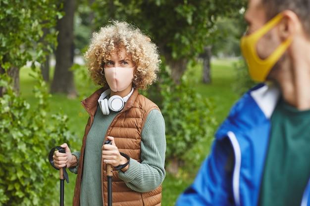 Giovane donna con capelli ricci in maschera protettiva utilizzando bastoni durante la passeggiata sportiva con il giovane all'aperto