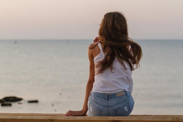 Giovane donna con i capelli ricci seduta sulla spiaggia mattutina e aspetta l'alba