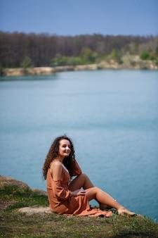 Una giovane donna con i capelli ricci e un sorriso sul viso siede in un prato verde sullo sfondo di un lago blu. calda giornata estiva, ragazza felice, emozioni di gioia