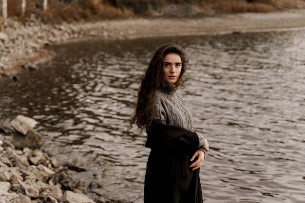 Giovane donna con i capelli ricci in piedi vicino al lago