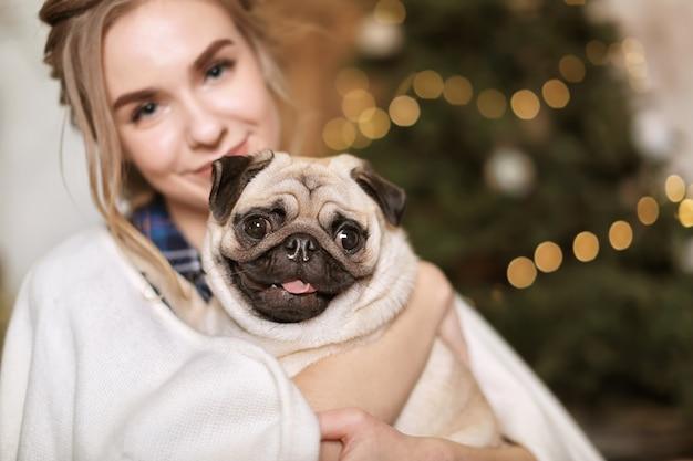 Giovane donna con un simpatico cagnolino a casa