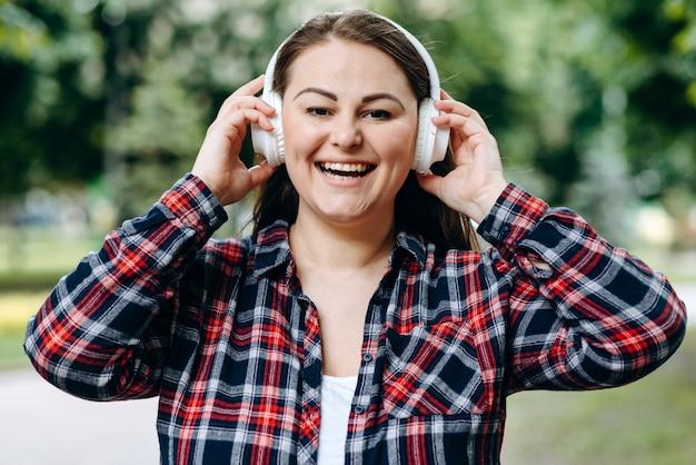 Giovane donna con le cuffie da portare di sorriso sveglio contro la città