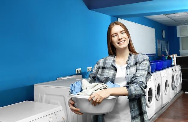 Giovane donna con vestiti sporchi in lavanderia a gettoni. giorno di bucato