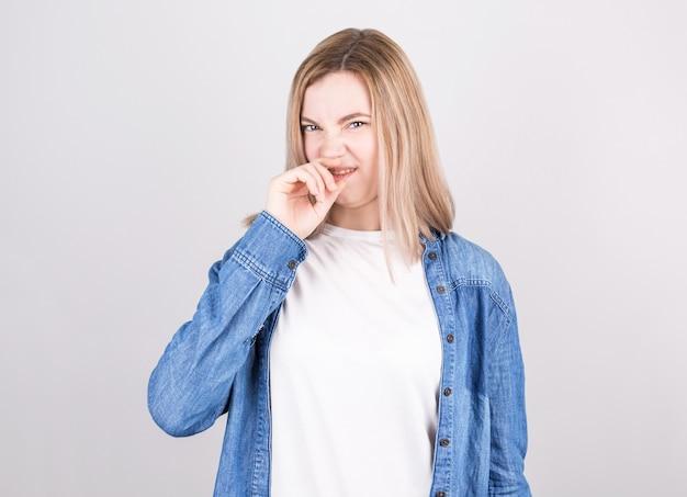 Giovane donna con disgusto sul viso pizzica il naso. espressione facciale di emozione negativa.