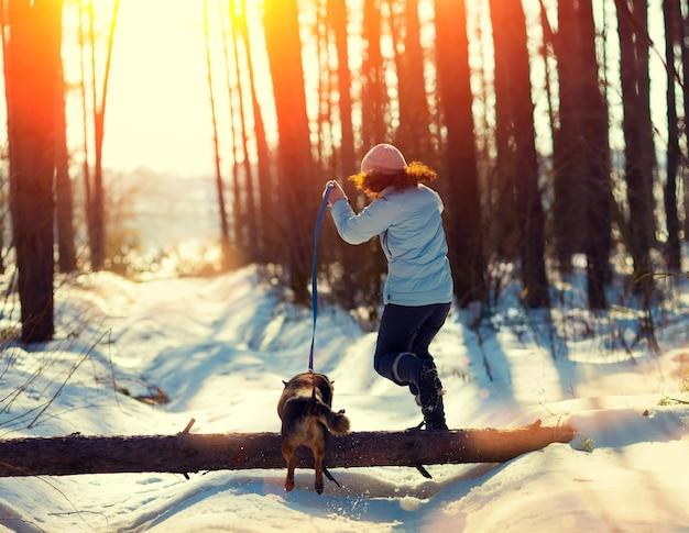 Giovane donna con cane che salta su un tronco