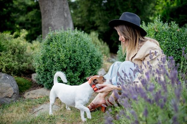Giovane donna con cane seduto in un giardino