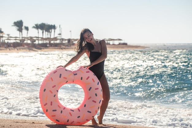 Una giovane donna con un cerchio di nuoto a forma di ciambella in riva al mare. il concetto di svago e intrattenimento in vacanza.