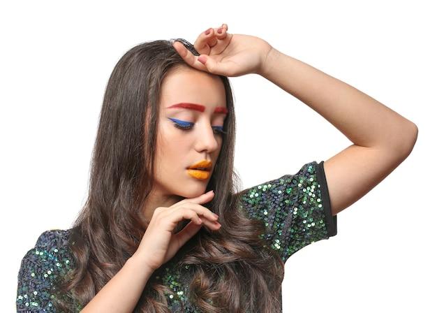 Giovane donna con le sopracciglia tinte e trucco creativo su bianco