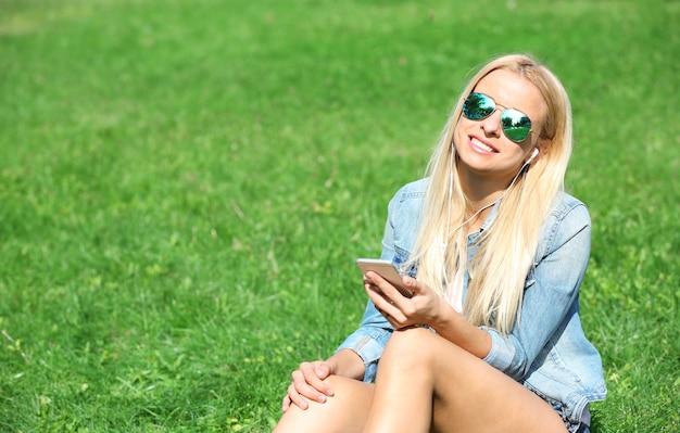 Giovane donna con auricolari e smartphone che ascolta musica sull'erba