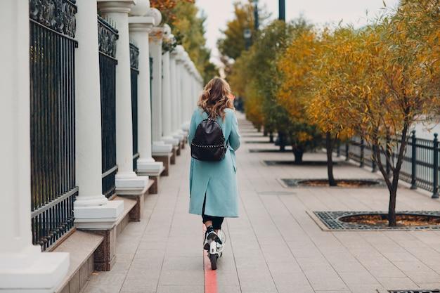 Giovane donna con scooter elettrico in cappotto blu presso la pista ciclabile sulla città