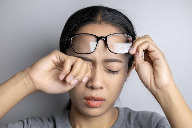 Giovane donna con dolore agli occhi su uno sfondo grigio. la donna asiatica soffre di dolore agli occhi. le donne tengono gli occhiali e soffrono di dolore agli occhi.