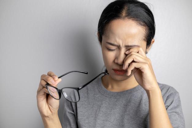 Giovane donna con dolore agli occhi su un grigio.