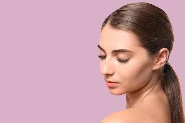 Giovane donna con le estensioni delle ciglia sulla superficie del colore