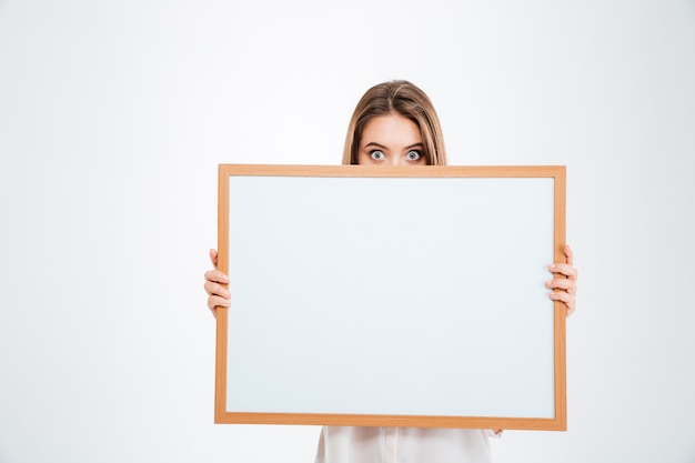 Giovane donna con gli occhi spalancati che fa capolino dal bordo bianco isolato su un muro bianco