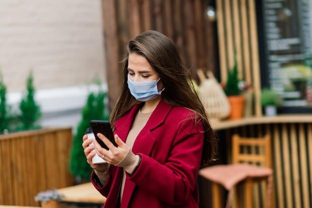 Giovane donna con una maschera facciale al ristorante, nuovo concetto normale per proteggere la pandemia di coronavirus