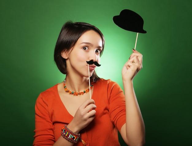 Giovane donna con baffi finti e cappello