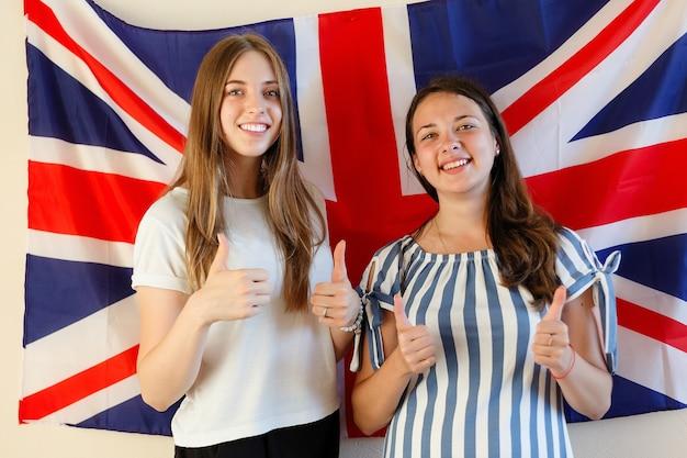 Giovane donna con bandiere di paesi di lingua inglese. studentessa inglese con la bandiera britannica sullo sfondo. inglese, impara, studia.