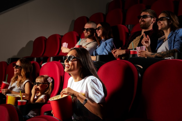 Giovane donna con gli amici a guardare film nel cinema