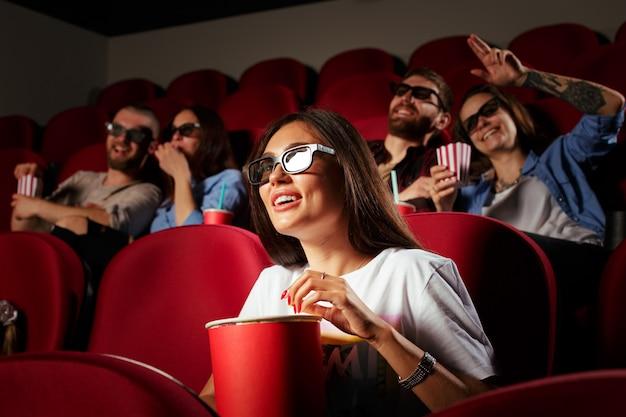 Giovane donna con gli amici a guardare film al cinema