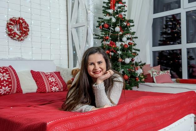 Giovane donna con confezione regalo in posa in studio di natale