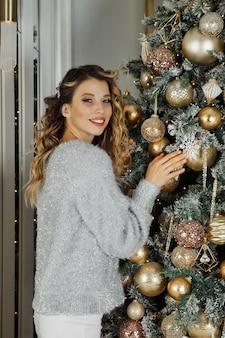 Giovane donna con regalo in piedi all'albero di natale felice e guardando la fotocamera. colore bianco argento sullo sfondo del soggiorno e del camino per buon natale e felice anno nuovo. momenti atmosferici