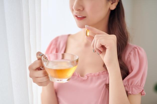 Giovane donna con un bicchiere d'acqua che prende la pillola vitaminica a casa