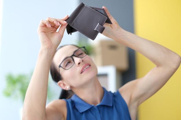 Giovane donna con gli occhiali che guarda il portafoglio vuoto a casa