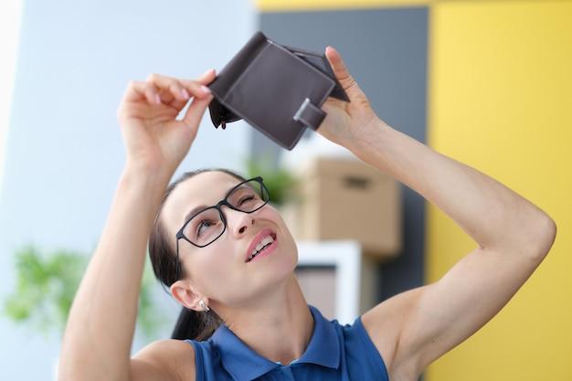 Giovane donna con gli occhiali che guarda nel portafoglio in pelle vuoto