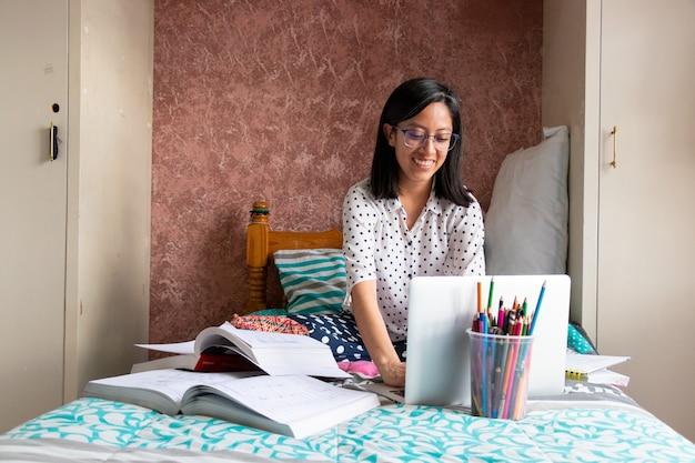 Una giovane donna con gli occhiali che guarda e scrive al computer seduta sul letto nella sua camera da letto, usando libri e matite colorate