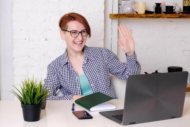 La giovane donna con gli occhiali si siede davanti allo schermo del computer portatile nel concetto dell'ufficio di apprendimento online