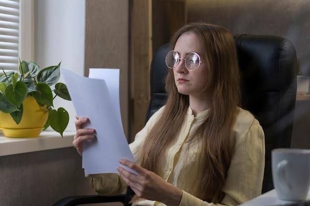 La giovane donna con gli occhiali si siede in un ufficio e legge il rapporto di lavoro, l'accordo o il contratto.
