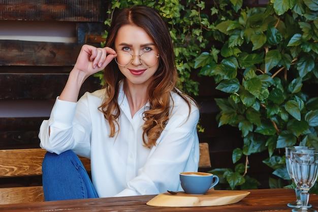 Giovane donna con gli occhiali si siede a un tavolo in un caffè