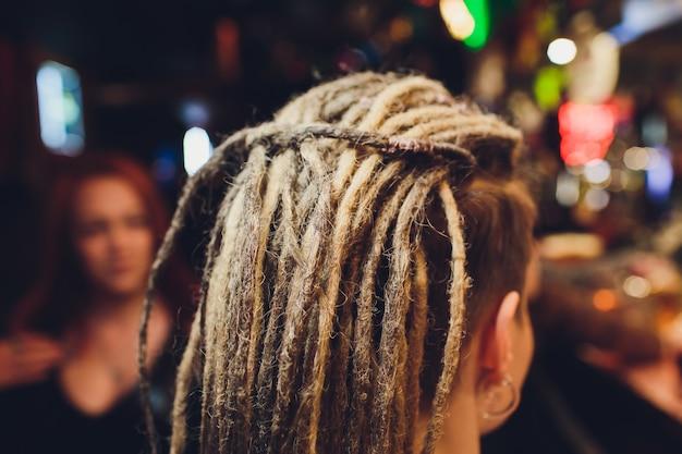 Giovane donna con trecce grigie capelli lunghi.