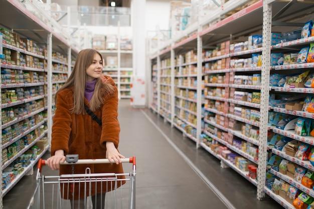 Giovane donna con carrello della spesa e scaffali con generi alimentari in un negozio.