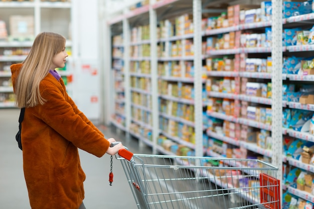 Giovane donna con carrello della spesa e scaffali con generi alimentari in un negozio