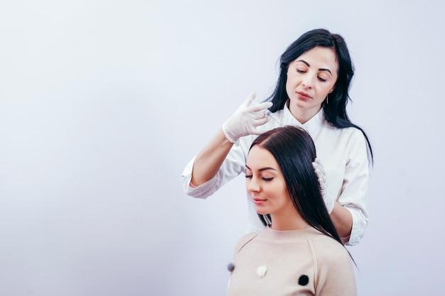 Giovane donna con problema di perdita di capelli che riceve l'iniezione, primi piani
