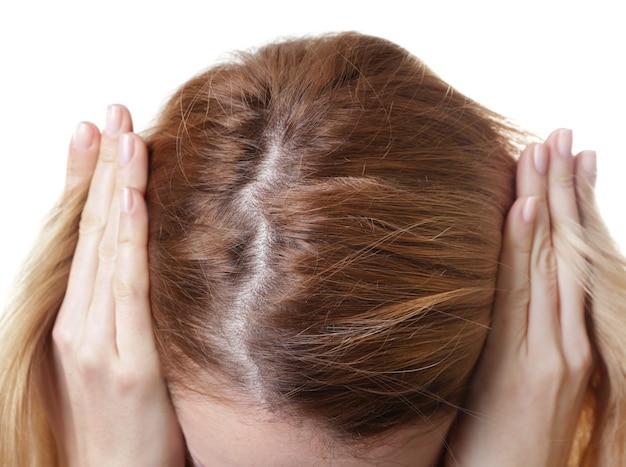 Giovane donna con problema di perdita di capelli su sfondo bianco, primo piano