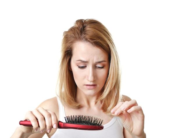 Giovane donna con problemi di perdita di capelli su sfondo bianco