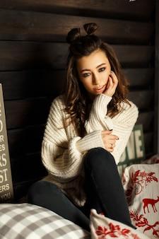 Giovane donna con un taglio di capelli in un maglione vintage lavorato a maglia che riposa in camera da letto sul letto con decorazioni natalizie