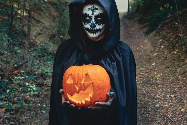 Giovane donna con la maschera per il viso di vernice di halloween indossando il cappuccio nero