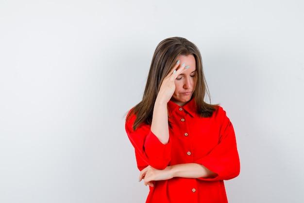 Giovane donna con le mani sul viso, chiudendo gli occhi in camicetta rossa e guardando sconvolto, vista frontale.