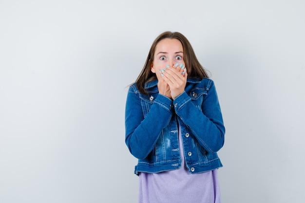 Giovane donna con le mani sulla bocca in giacca di jeans e sembra spaventata. vista frontale.