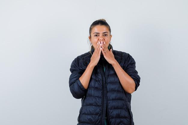 Giovane donna con le mani sulla bocca in piumino e dall'aria interrogativa. vista frontale.