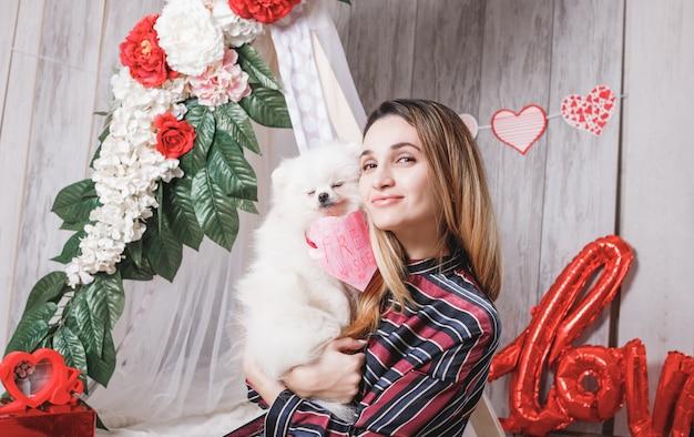 Giovane donna con felice carino soffice cane bianco (pomerania) con baci gratis cuore di carta, concetto di san valentino.