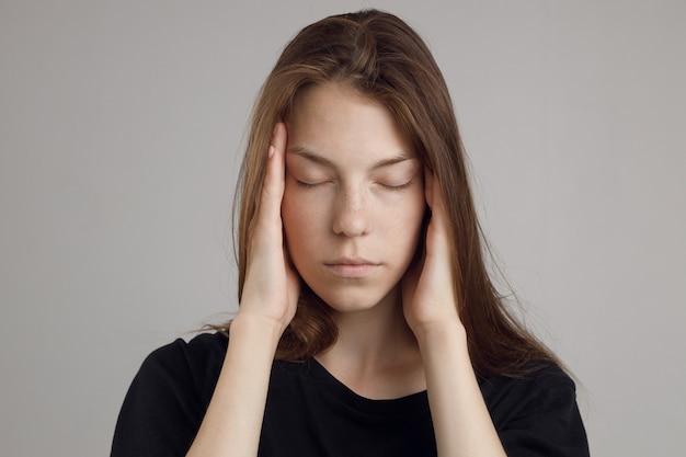Una giovane donna con mal di testa, tenendo la testa, isolata su uno sfondo bianco. ritratto di ragazza, tema medico, dolore alle tempie.