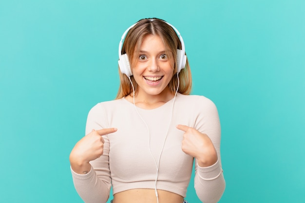 Giovane donna con le cuffie che si sente felice e indica se stessa con un'eccitazione