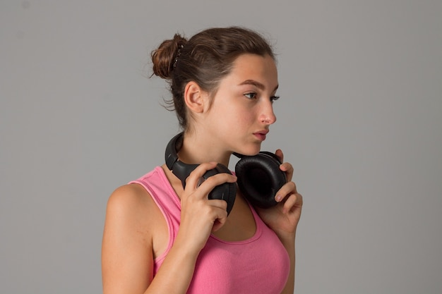 Giovane donna con le cuffie in studio sul muro grigio